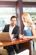 Working colleagues - a man and a woman - sitting in cafe