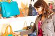 Frau kauft eine Tasche in einer Mall