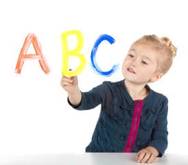 Little girl paints letters on window
