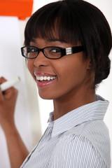 Woman with glasses writing on blackboard