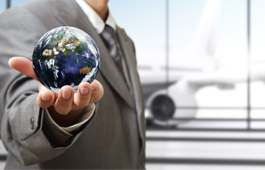 """business man holds globe in the airport""""Elements of this image f"""