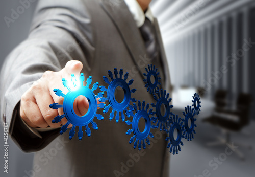 business man hand point cogs icons in board room