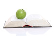 Green apple over a open book isolated on white