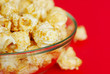 Popcorn in the plate on red background