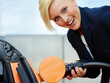 Business woman is loading electrically powered car outdoors