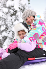 Mother and daughter sledging together