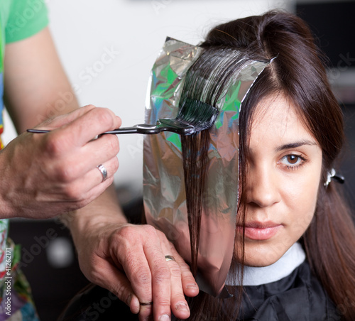 Hairdresser coloring woman's hair. Selective focus