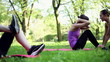 women doing sit-ups, exercising with personal trainer