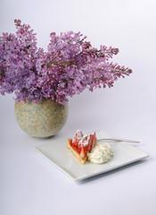 Erdbeer-Torte auf einem Kuchenteller neben einem Fliederstrauß