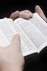 closeup of the hands of a man holding russian bible