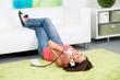 frau liegt entspannt auf dem teppichboden und telefoniert