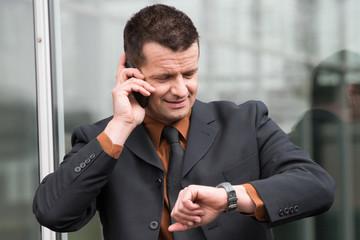 manager telefoniert und schaut auf die uhr