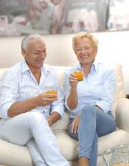 Pareja adulta bebiendo jugo de naranja en casa.