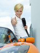 Pretty woman loading electrically powered car and shows thumb up