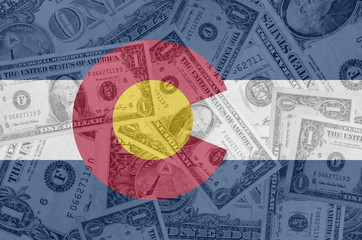 US state of colorado flag with transparent dollar banknotes in b