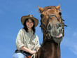 cheerful cowgirl with dissatisfied horse