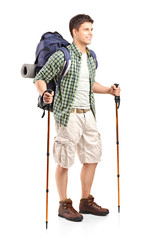 Hiker with backpack holding hiking poles