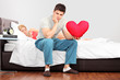 Man in thoughts holding a heart shaped pillow while his girlfrie