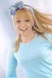 Portrait of a happy young blonde woman in blue shirt