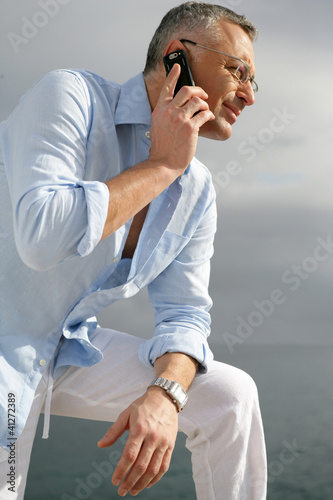 Man admiring the coastal view whilst making a telephone call
