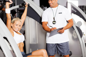 personal trainer and customer in gym