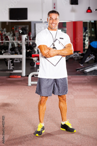 handsome male gym trainer portrait inside gym