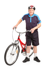Senior bicyclist posing next to a bicycle