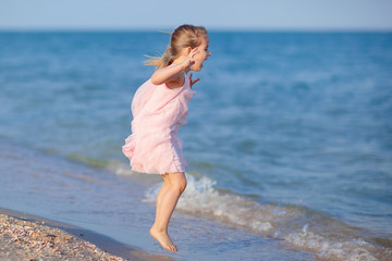 Adorable child walking beach shore splashing water in blue sea