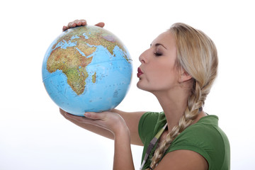 Woman in a green top kissing a globe