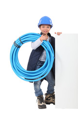 Young boy dressed as a plumber with a board for message