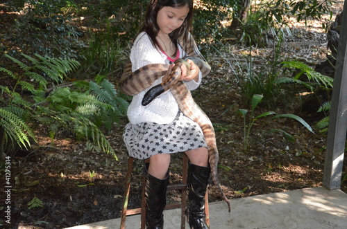 Little girl is holding a python in her arms