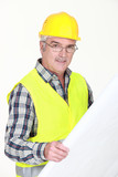 A mature foreman checking plans.