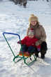 Happy mother with toddler on sled