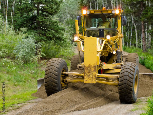 Grader resurfacing narrow rural road