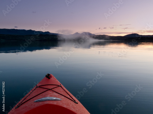Paddling in a kayak through calm sunset waters