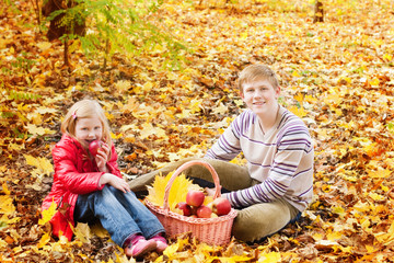 brother and sister in autumn garden