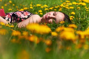 schlafende frau entspannnt mit einem buch draußen