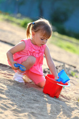Girl playing alone in the sandpit
