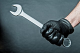 black leather glove and a spanner