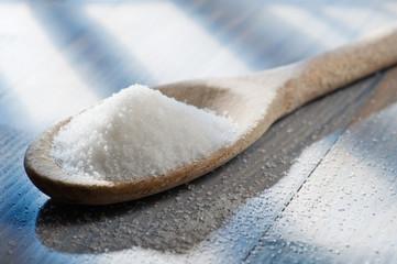 white sugar in wooden spoon