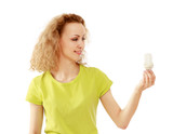 Pensive young woman looking at energy-saving bulb