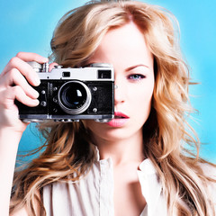 beautiful blond photographer woman holding retro camera