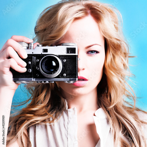 beautiful blond photographer woman holding retro camera