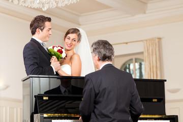 Brautpaar vor einem Klavier