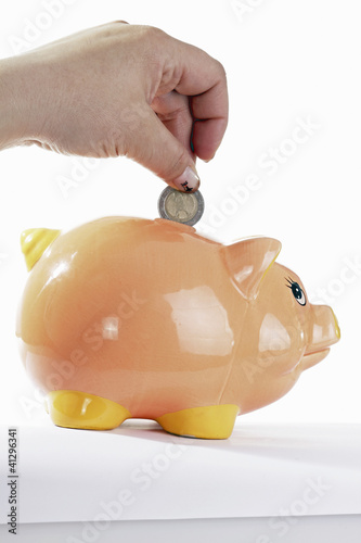 piggy bank with hand with euro coin on rhe white background