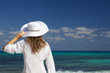 Woman with a white hat looking at the sea