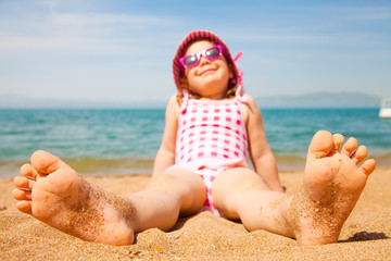 little girl lying on a sandy beach