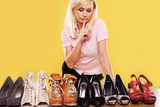 Blonde lady trying to decide which shoes to wear poster