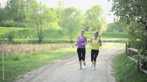 Two young girls jogging in the park