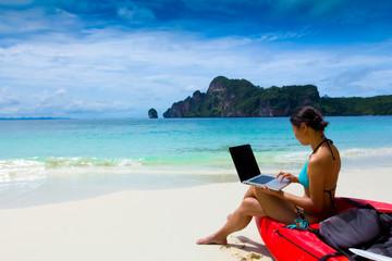 woman in bikini using laptop at the beach